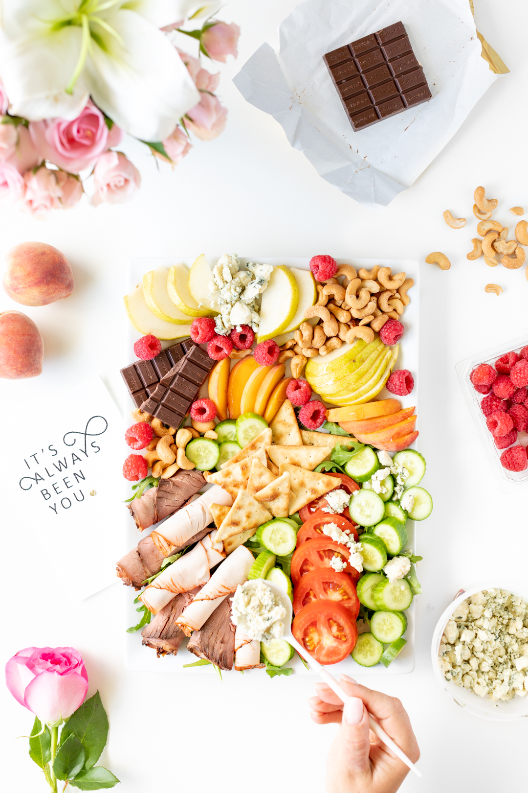 date night snack board with a variety of foods from pears, chocolate and raspberries.