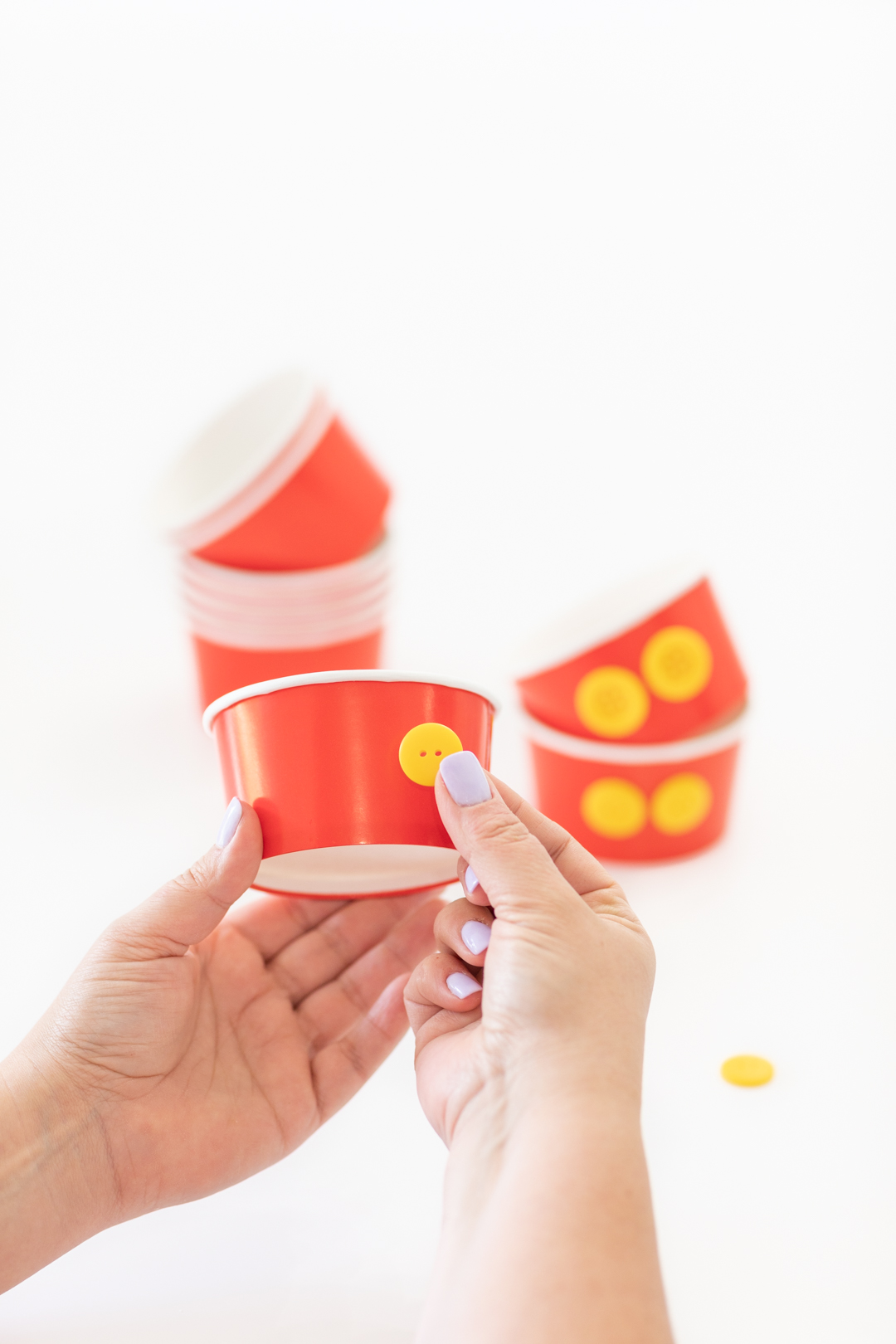 Press yellow buttons into red paper ice cream cups
