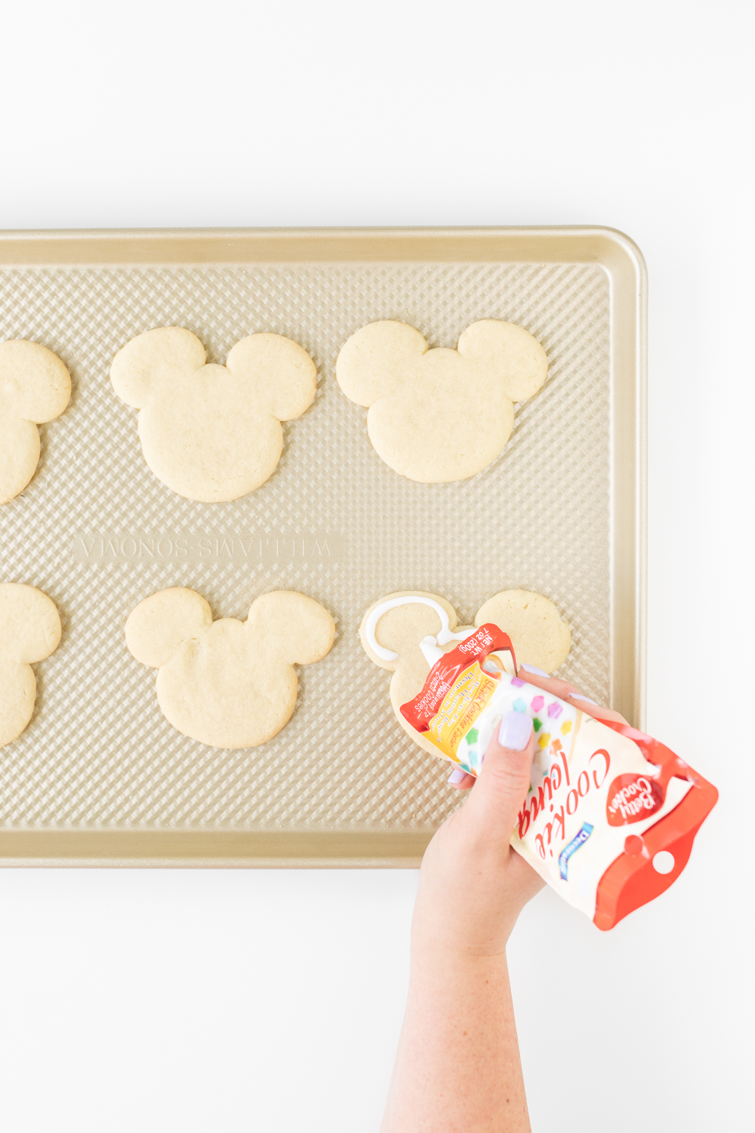 Adding icing to Mickey Mouse Cookies