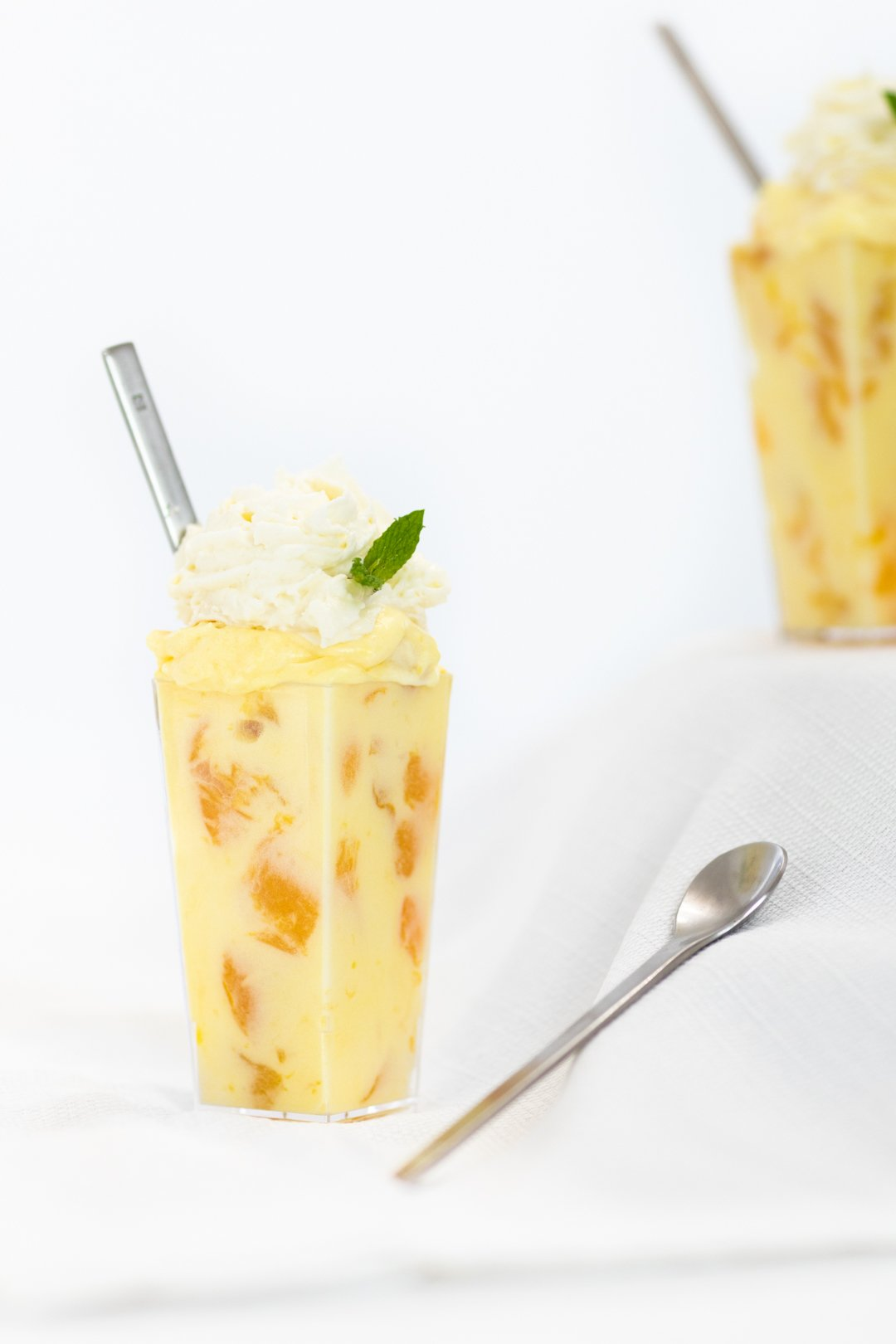 Peach pudding parfaits with a dash of mint for garnish