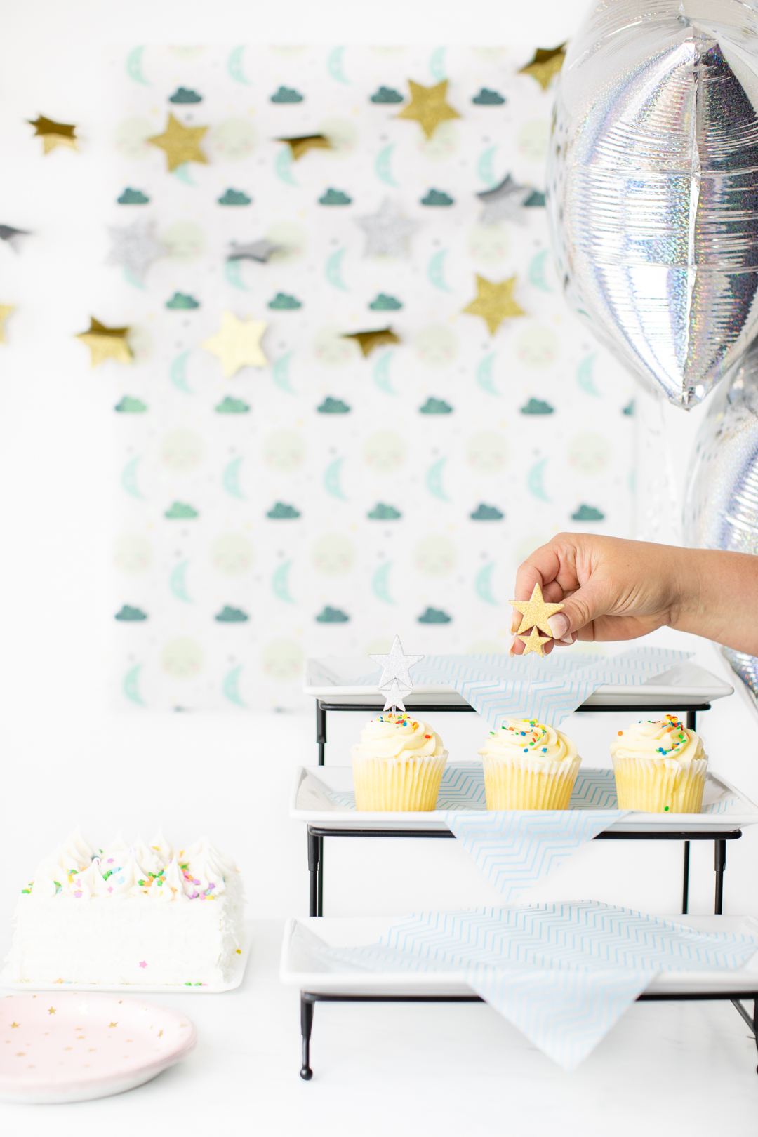 adding star cupcake topper to a cupcake