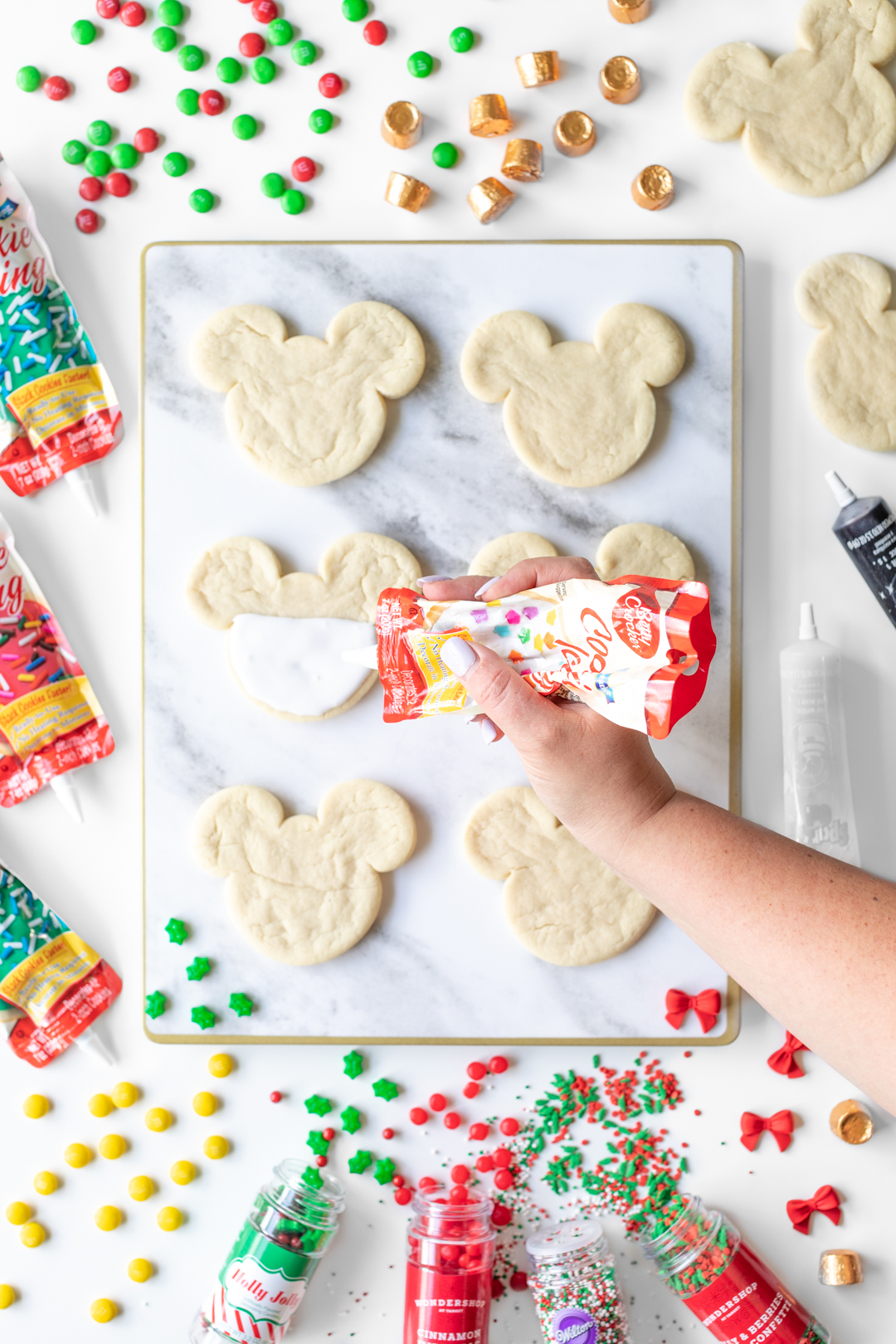 Adding icing onto Mickey Mouse cookie.