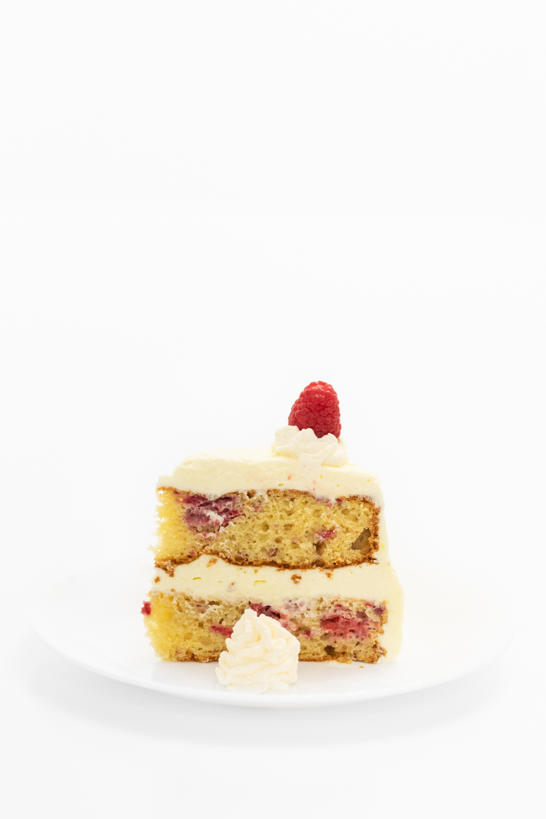 Pretty slice of fresh raspberry cake with lemon frosting.