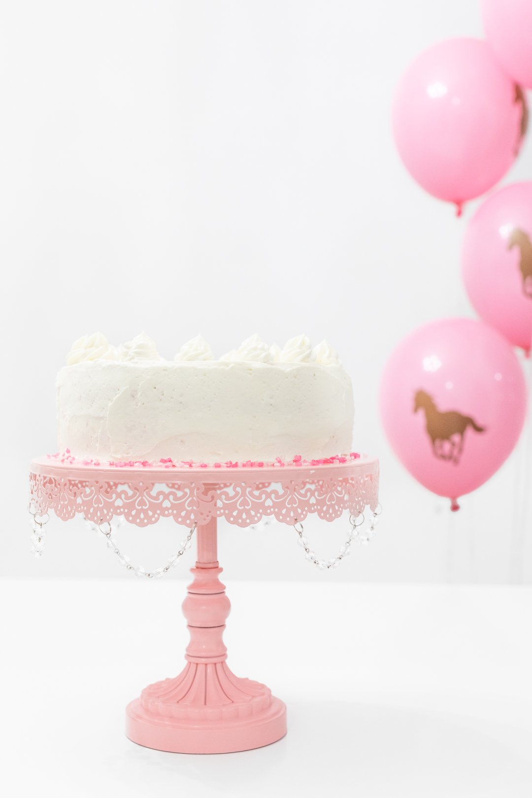 White cake on pretty pink cake stand. Horse balloons.