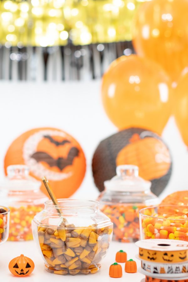 Halloween Treat Bag Station Table with Candy and Black Orange and Gold Halloween Decorations.