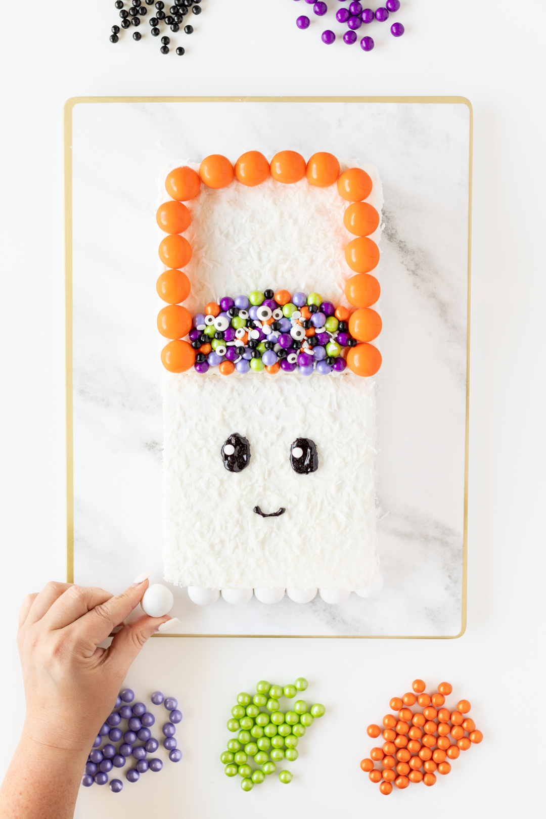 Adding gumballs to decorate a Halloween cake.