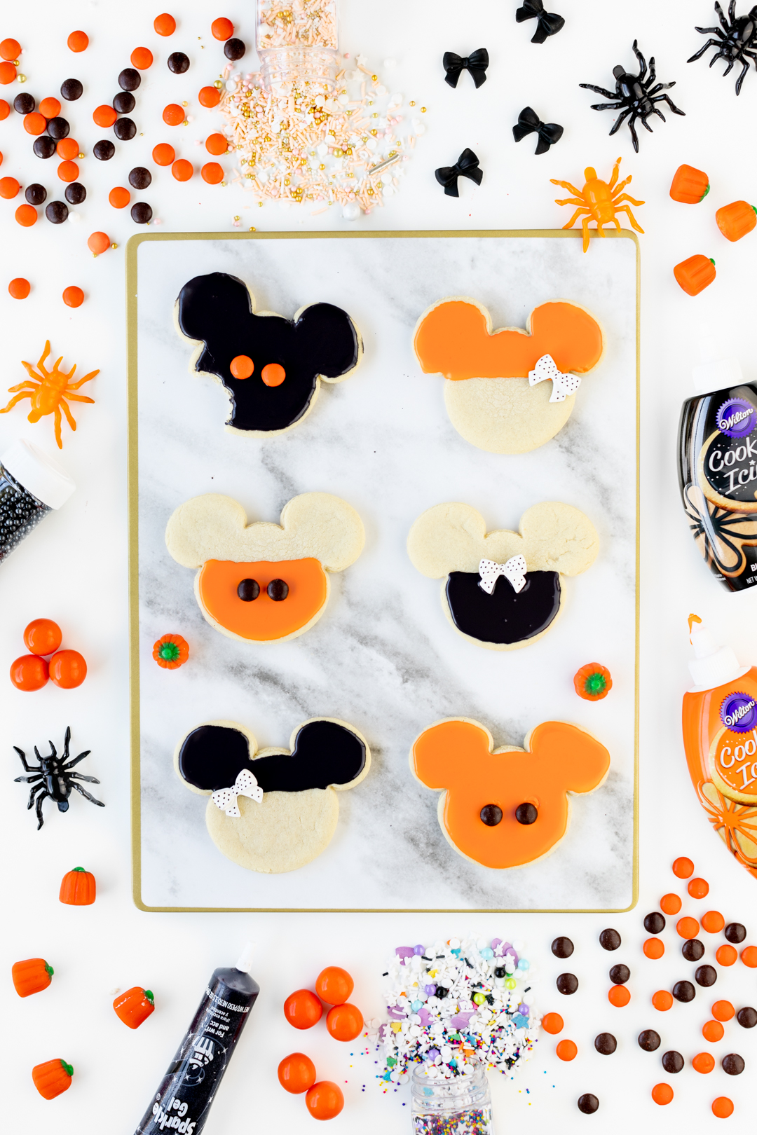 Mickey and Minnie Halloween Cookies decorated with orange and black icing and candies.
