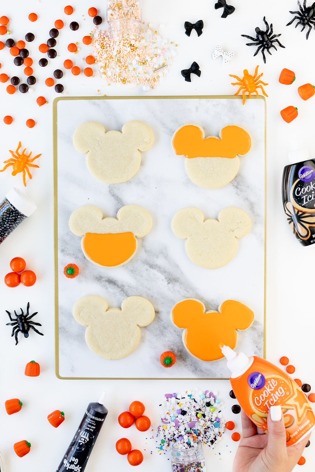 Adding orange icing to mickey mouse shaped cookies.