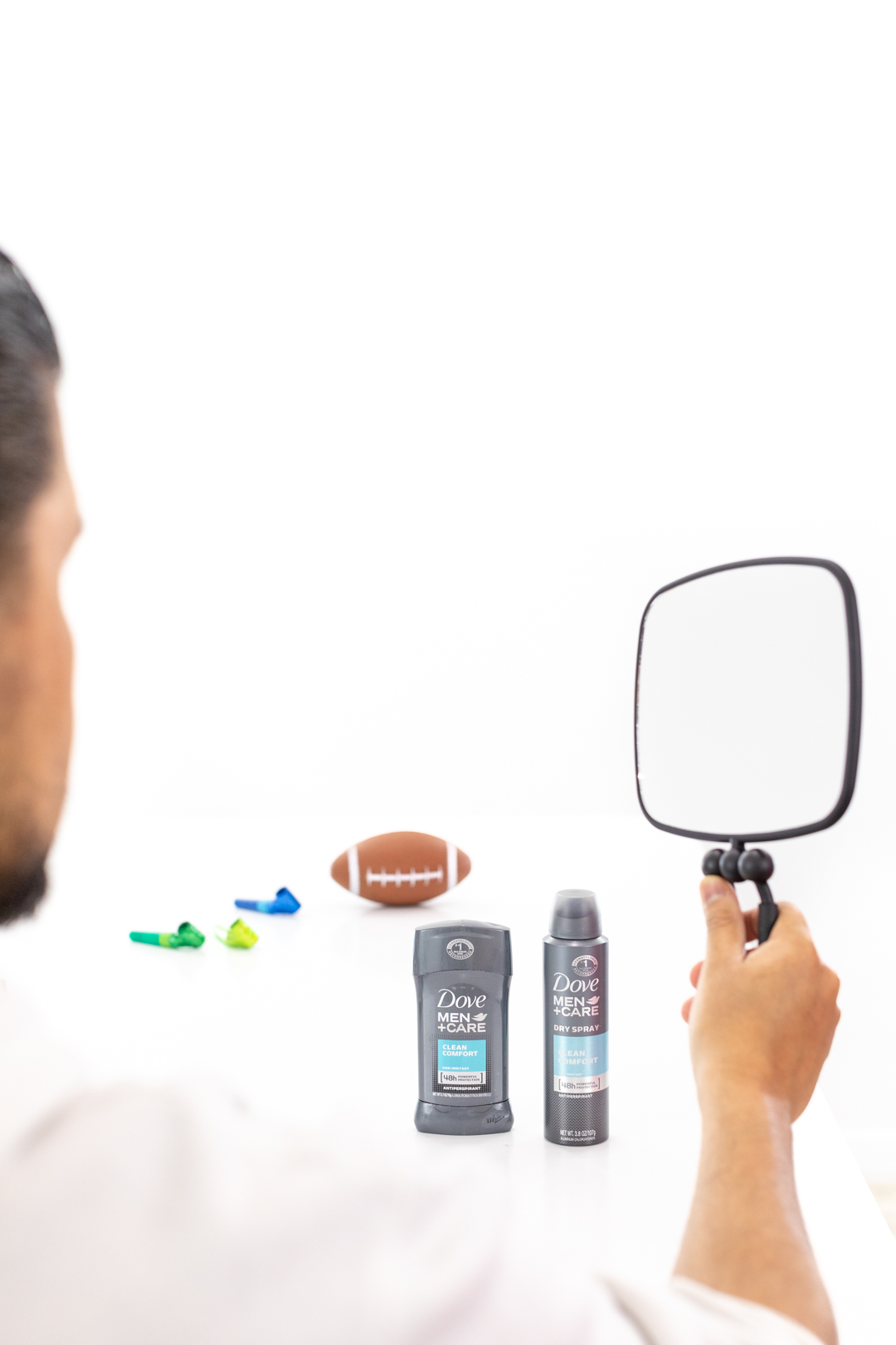 Man grooming with hand-held mirror.