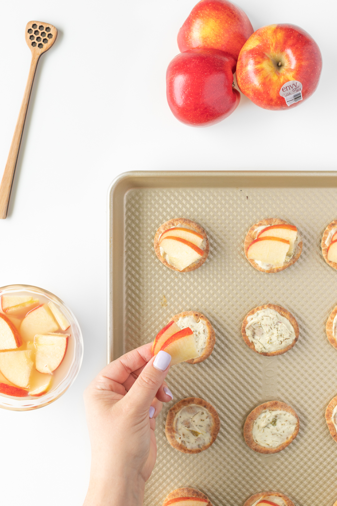 adding small slices of apples to mini pita appetizers