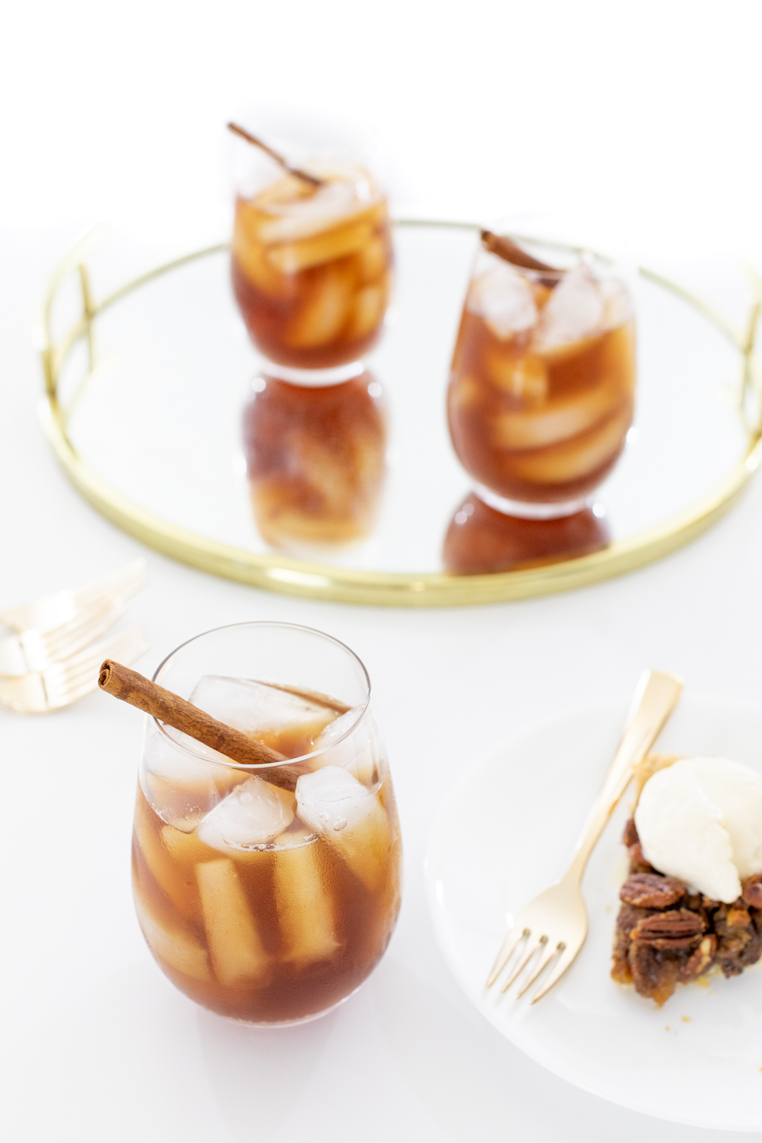 Glass of iced tea with ice and a cinnamon stick served with a slice of pecan pie with ice cream.