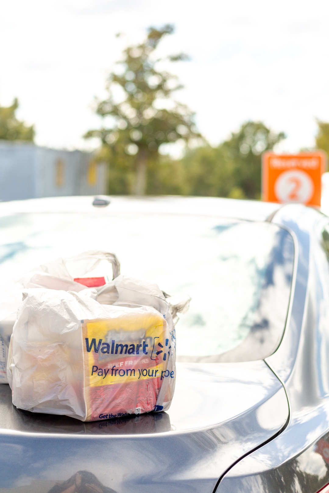 Walmart Online Grocery Pickup bags on top of a car