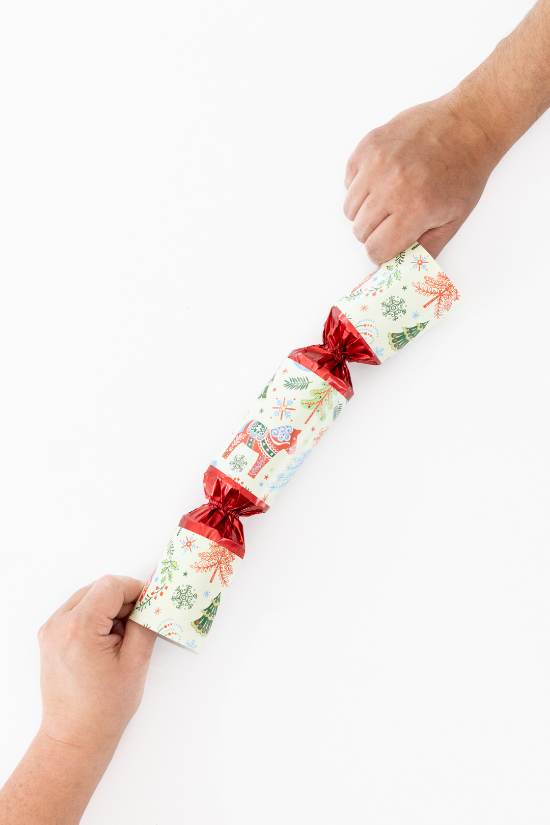 Two people tugging at a Christmas Cracker to demonstrate how to make it pop.