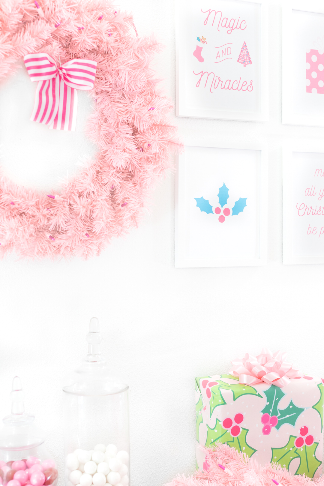 pink christmas decorations with wall art, wreath and pink garland.