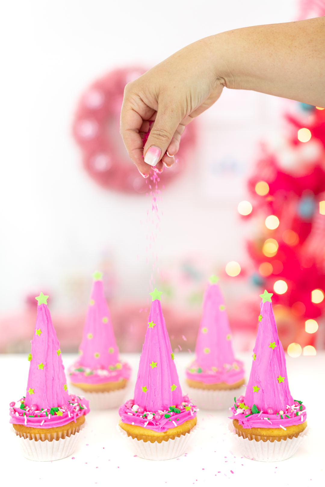 sprinkling pink sugar crystals over pink christmas tree cupcakes