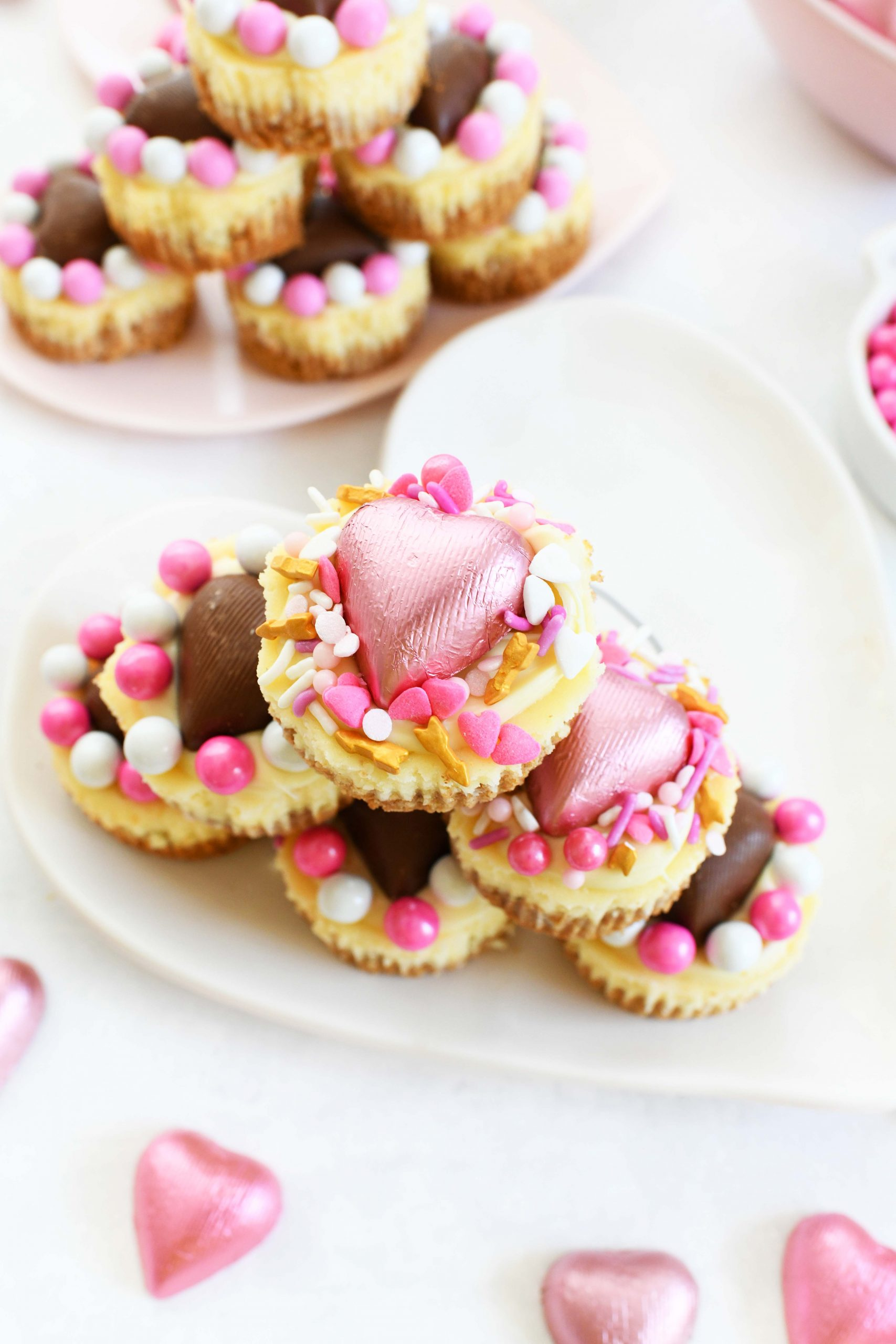 mini cheesecakes with valentine's day sprinkles and heart shaped chocolates on top.