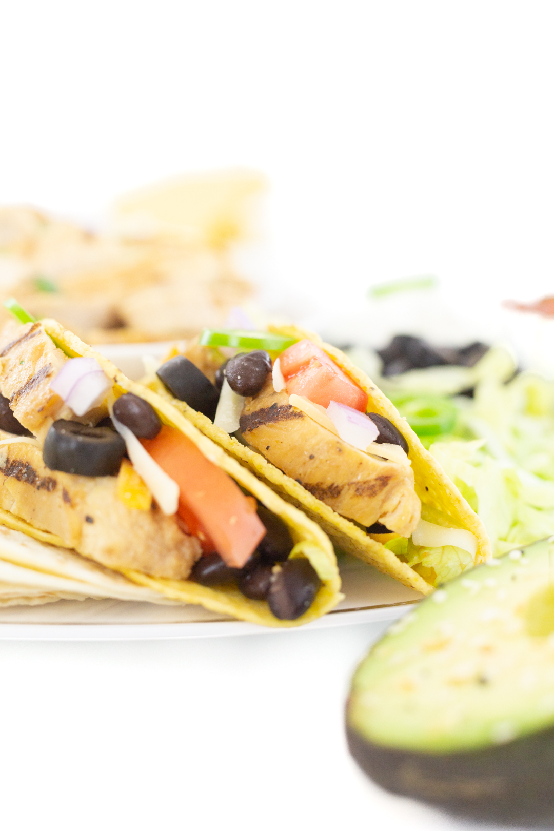 chicken tacos up close with tomatoes and black beans