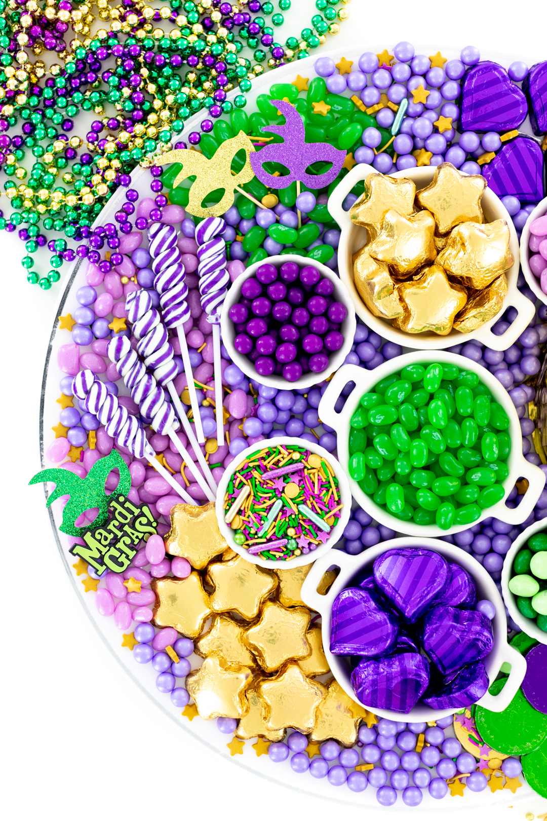 mardi gras candy grazing board with purple swirl lollipops and more green, purple and gold candies.
