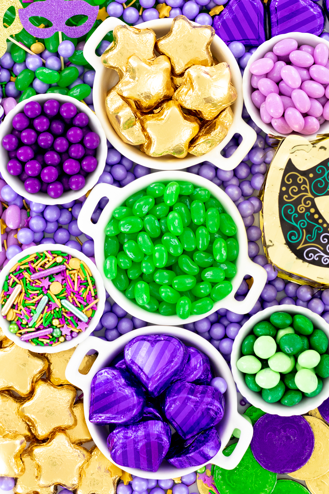 candy tray up close with gold foil star shaped chocolates, green jelly beans, mini M&Ms.
