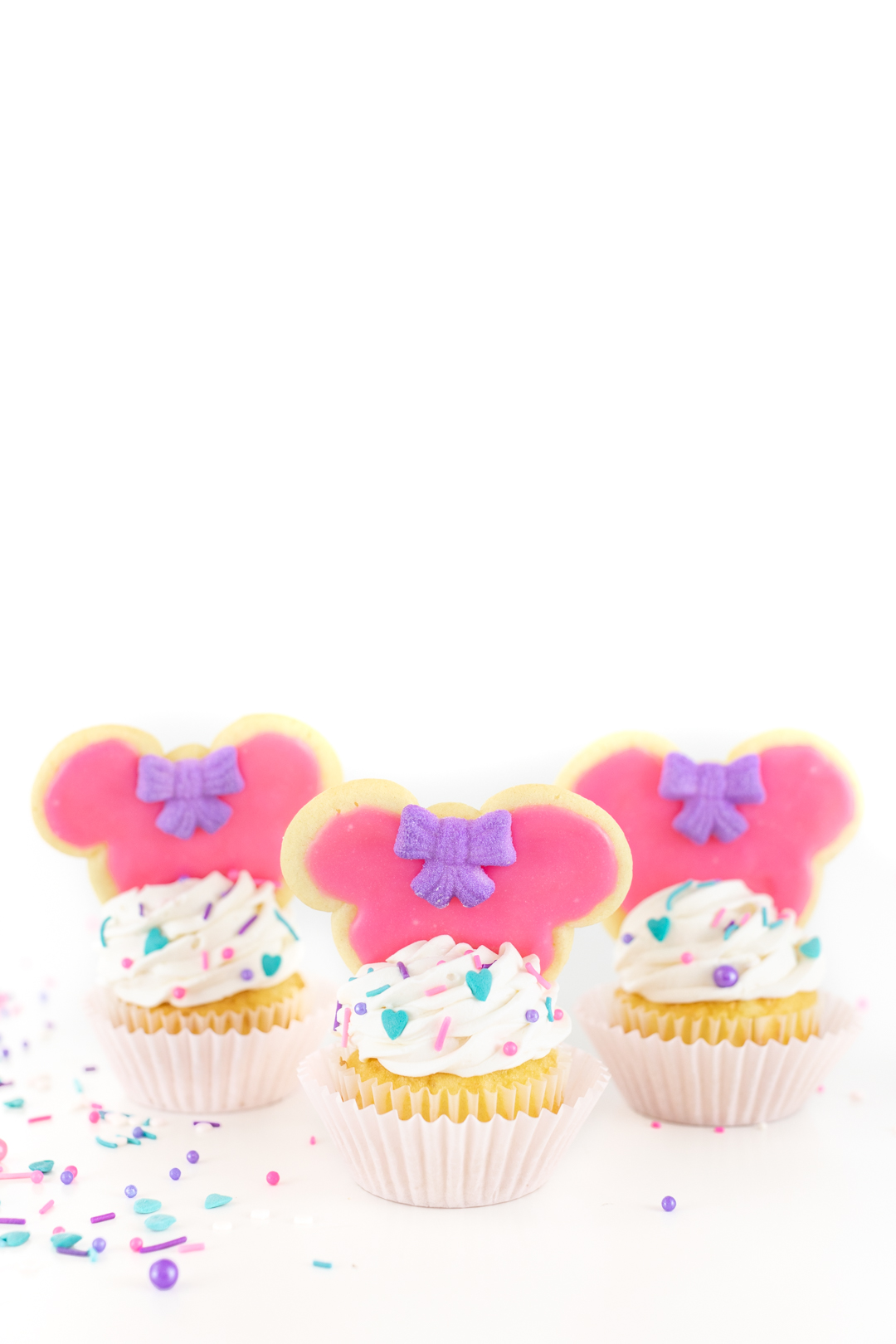 Adorable minnie mouse cookies placed on top of cupcakes
