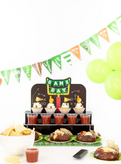 fun football party table with banner and balloons as well as food.