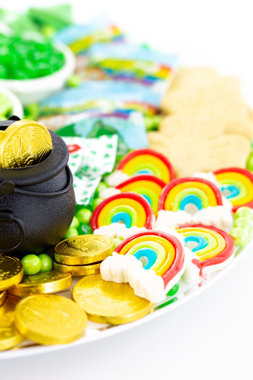 rainbow gummy candies and gold coins on a tray