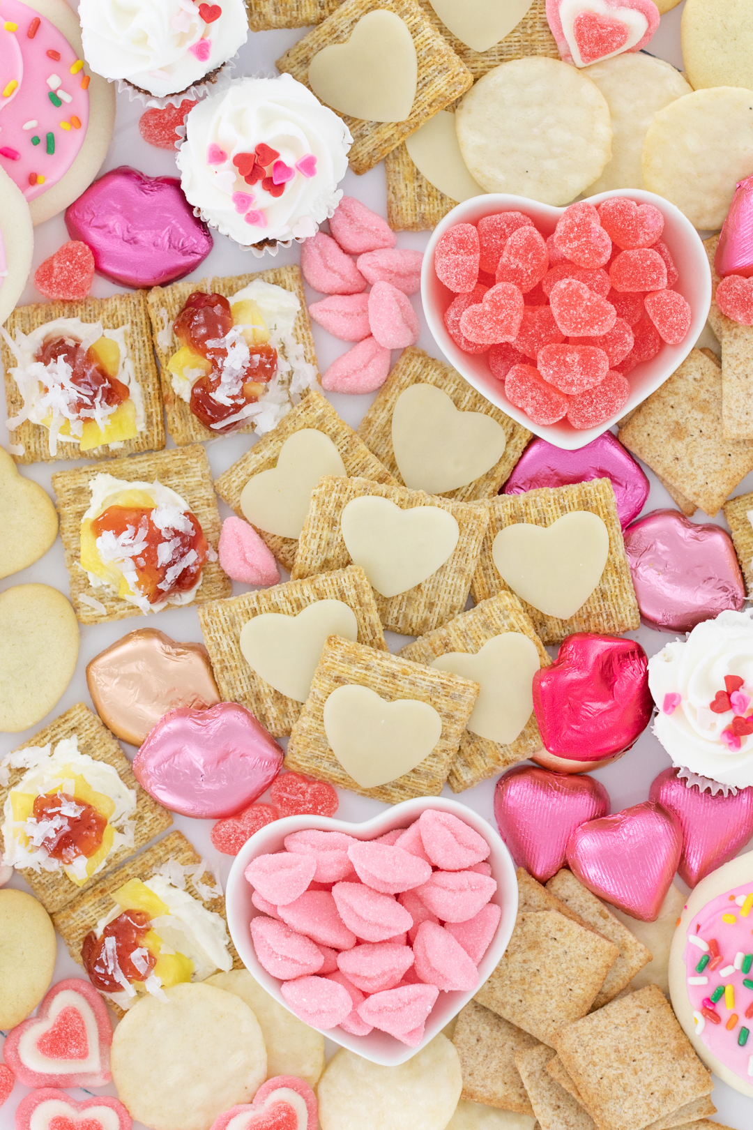 pretty snack board with heart shaped cookies and candies