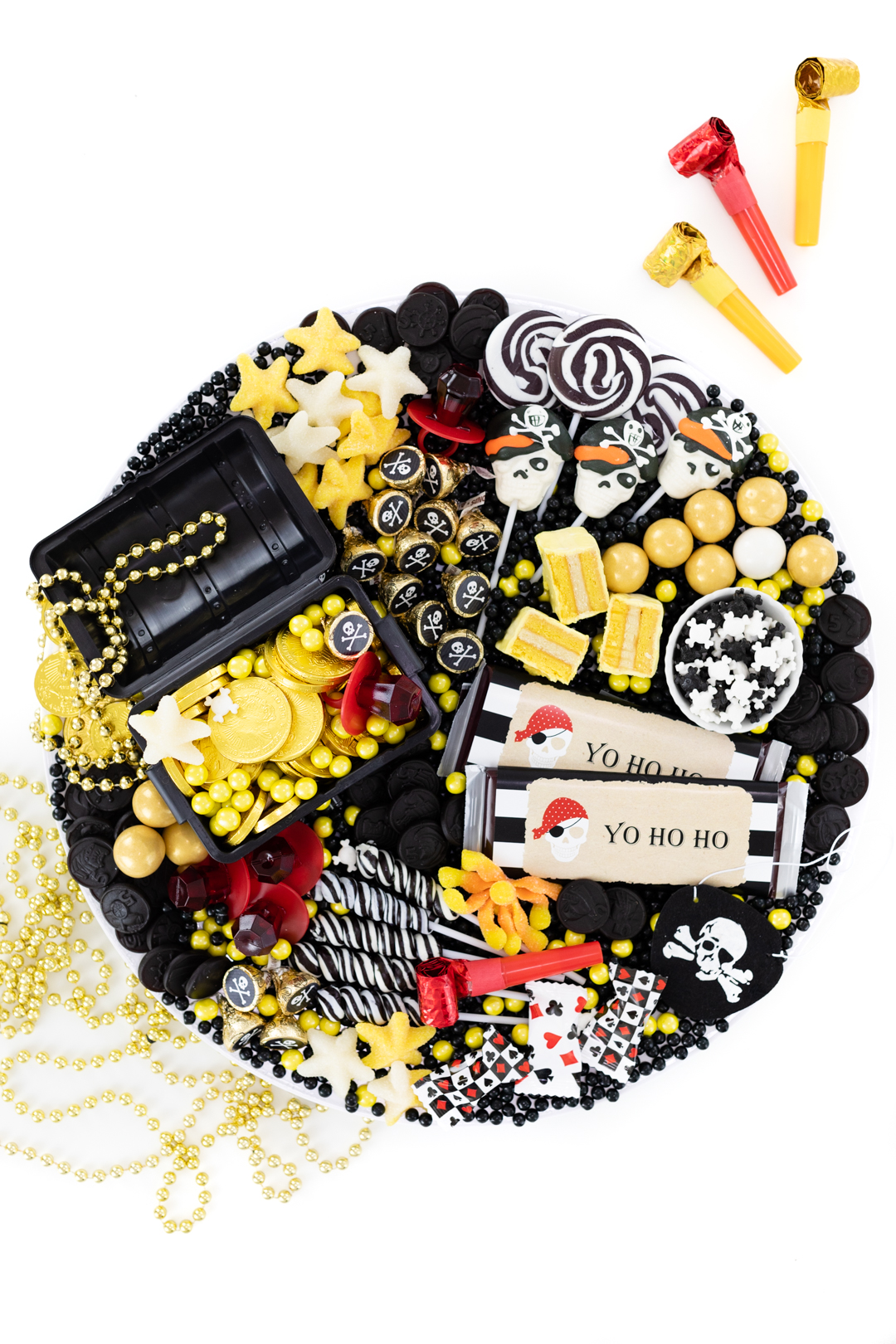 pirate charcuterie candy board with treasure chest, gold coin chocolates, black and white lollipops.