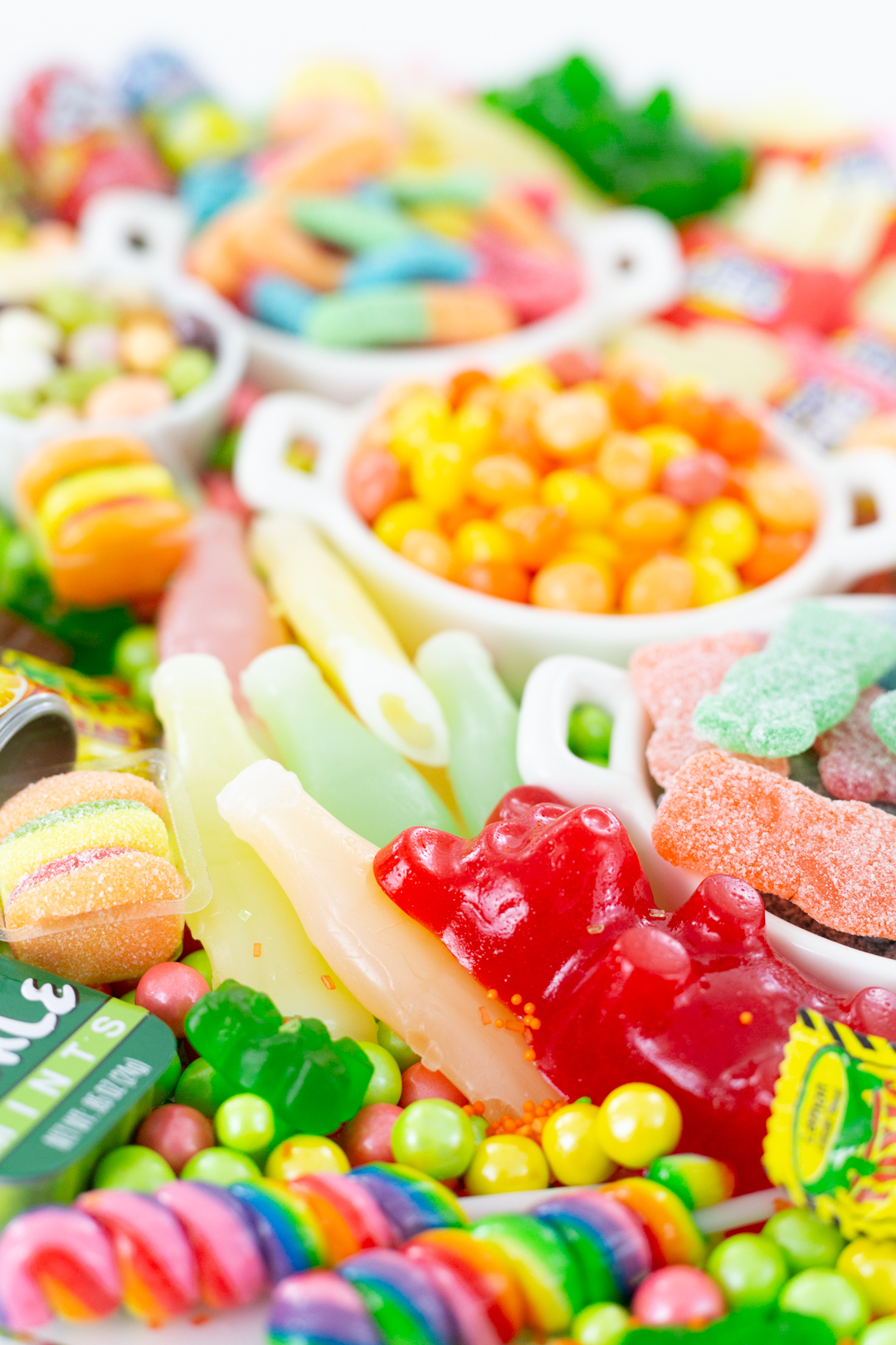 Funny tray of candies with giant gummy bear, colorful lollipops, soda candies.