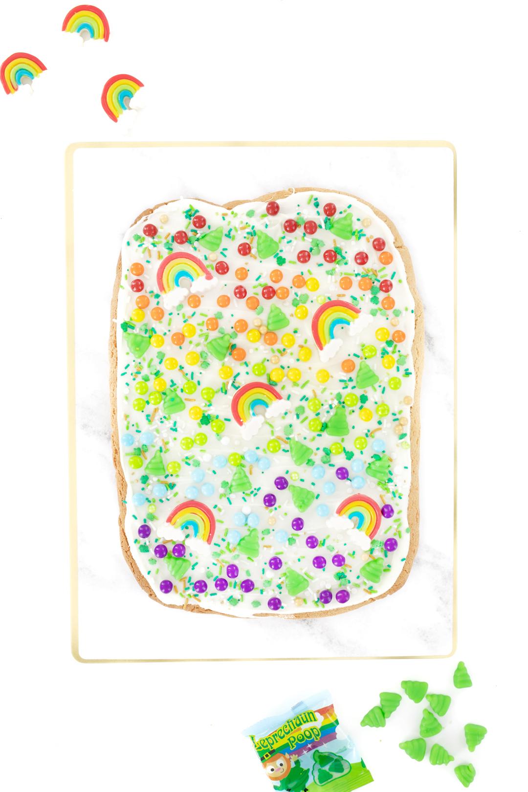 pretty rainbow cookie bark with rainbow candies, rainbow gummies and Leprechaun poop candies.