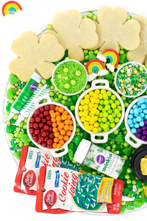 tray of unfrosted shamrock cookies and sprinkles and toppings