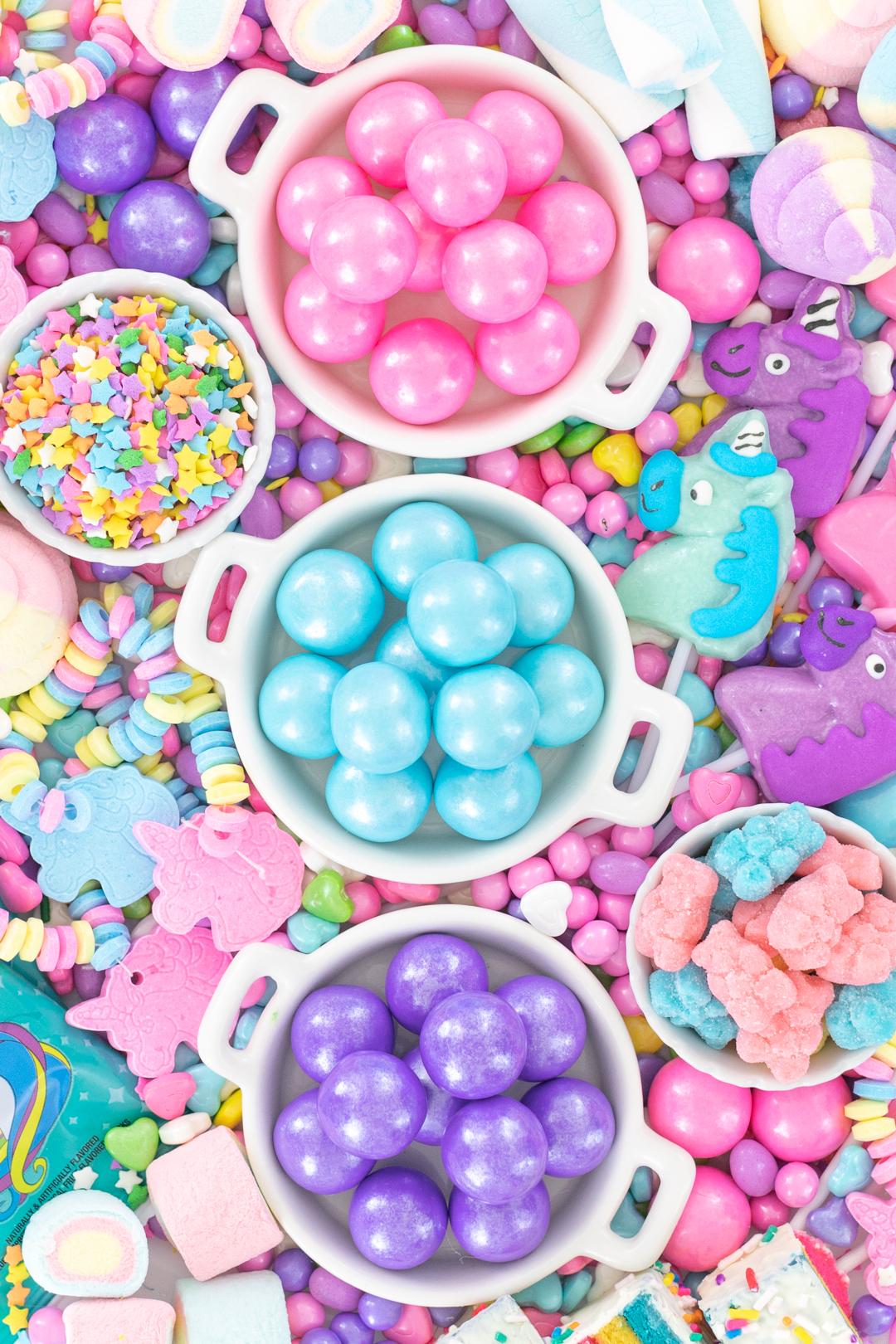 pretty tray of unicorn candy and gum. pink, blue, purple. unicorn candy bracelets