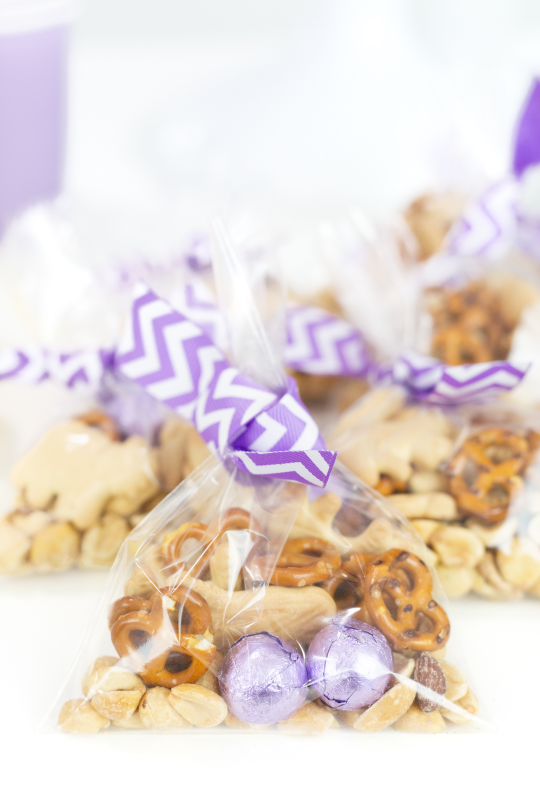 individual snack baggies with purple striped ribbon tied around