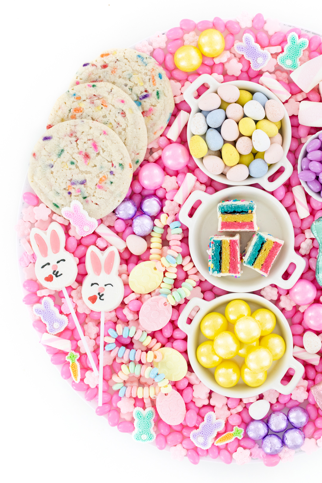 pretty easter candy tray with desserts and candies that are pastel colored