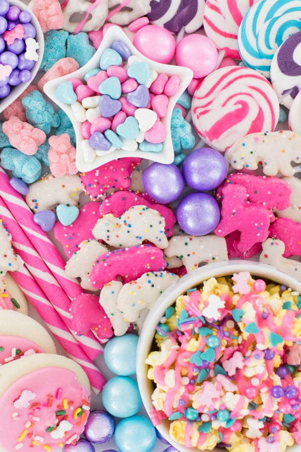 Tray filled with pastel candies, gumballs, cookies, pastel popcorn.