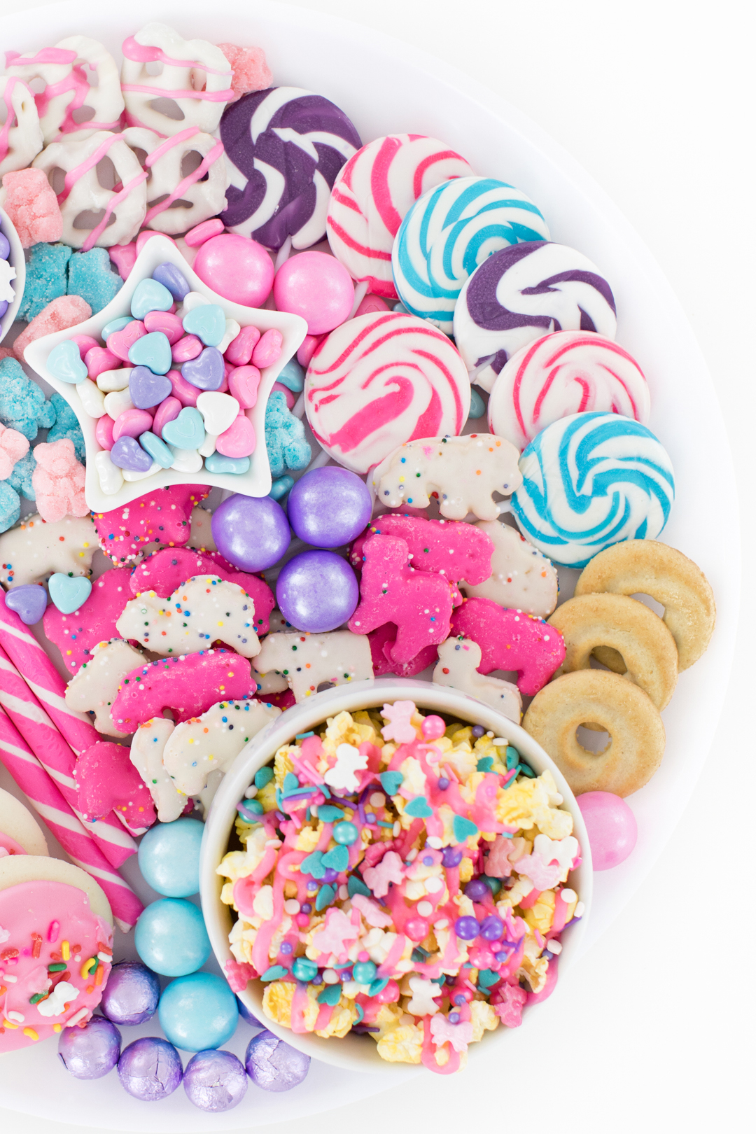 pastel snack board with lollipops and popcorn and cookies.