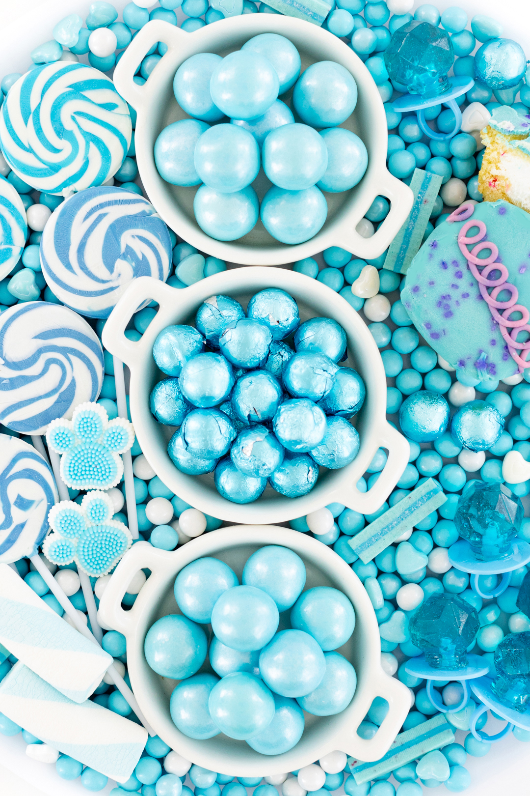 candies. Blue foil wrapped chocolates, gumballs, lollipops on a tray.