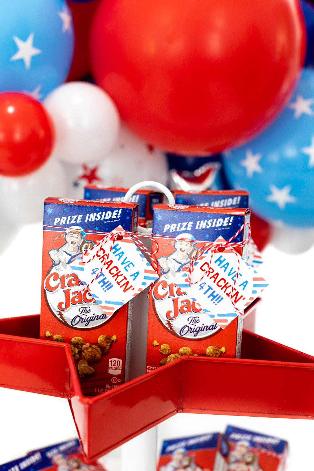 Individual boxes of cracker jack served on a 4th of july tray for parties. balloons in background