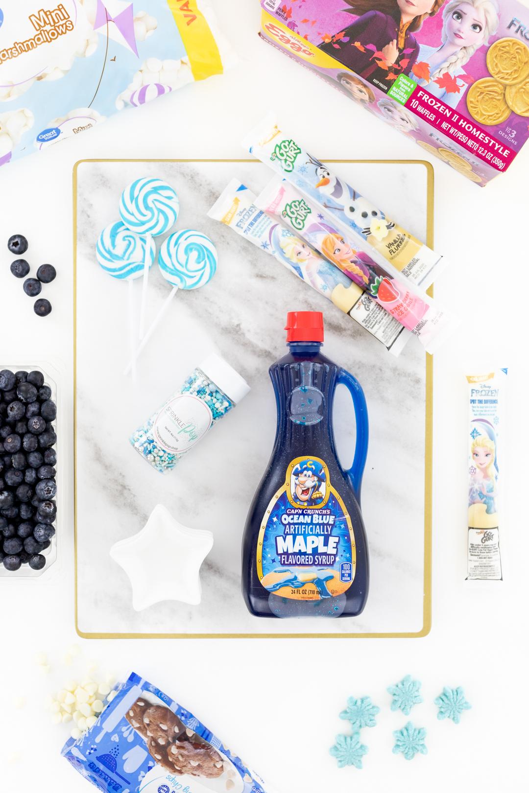 frozen movie waffle charcuterie items. Blue maple syrup, frozen movie gogurt, sprinkles, blueberries.