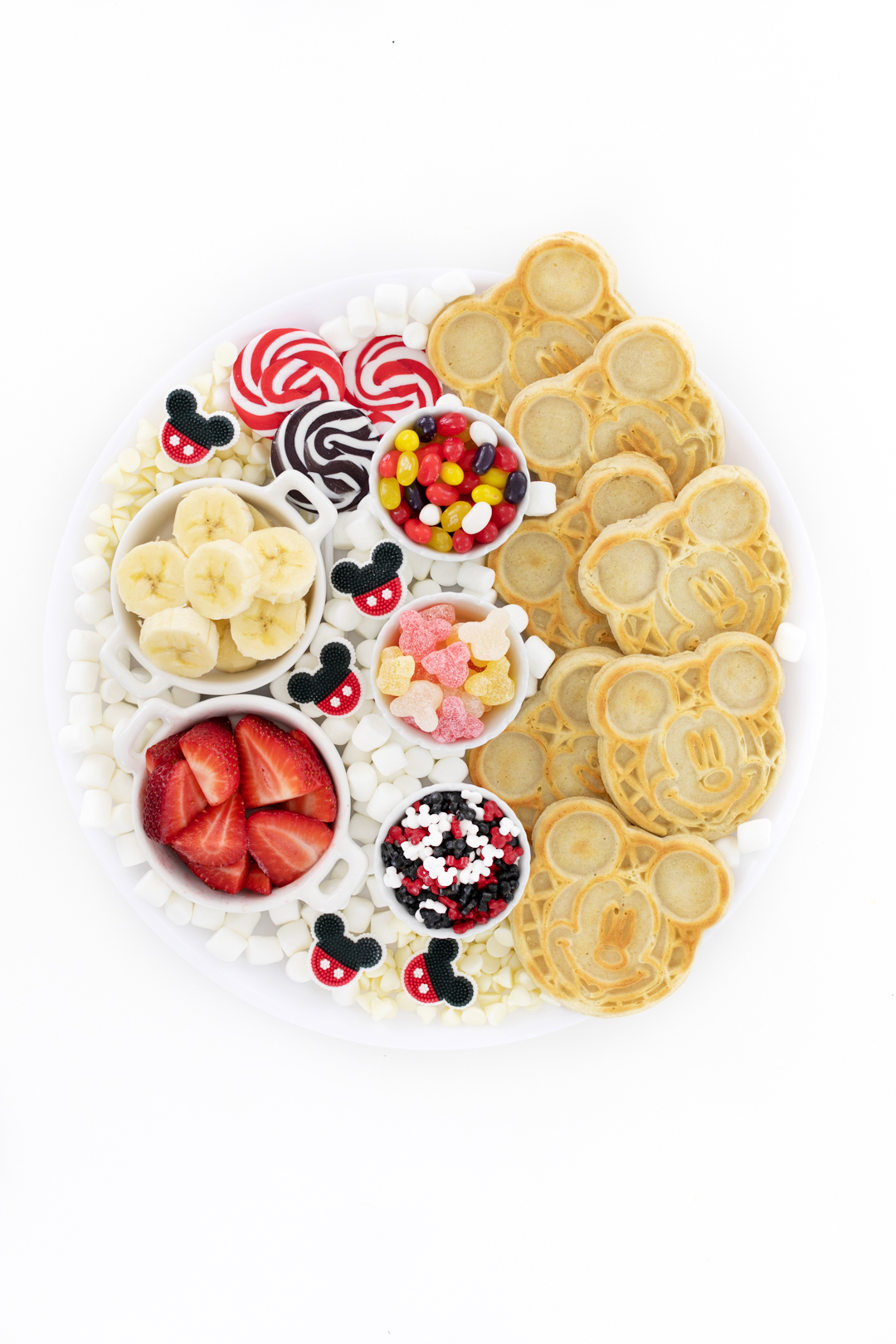 cute disney mickey mouse charcuterie board with waffles and waffle toppings including bananas and strawberries
