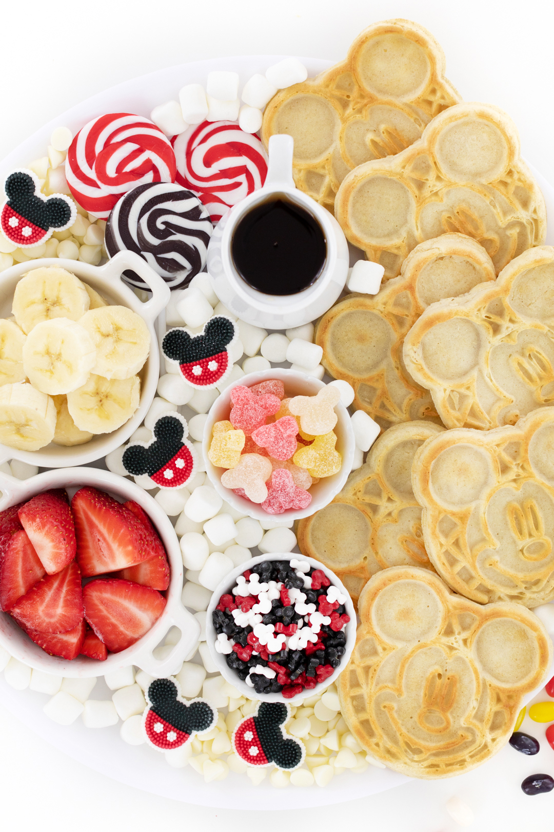 mickey mouse inspired breakfast with waffles that have mickey mouse on them and matching toppings in little dishes