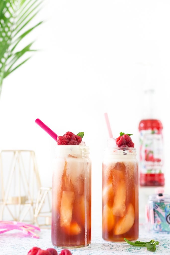 Pretty iced tea for summer with raspberries and pretty pink straws