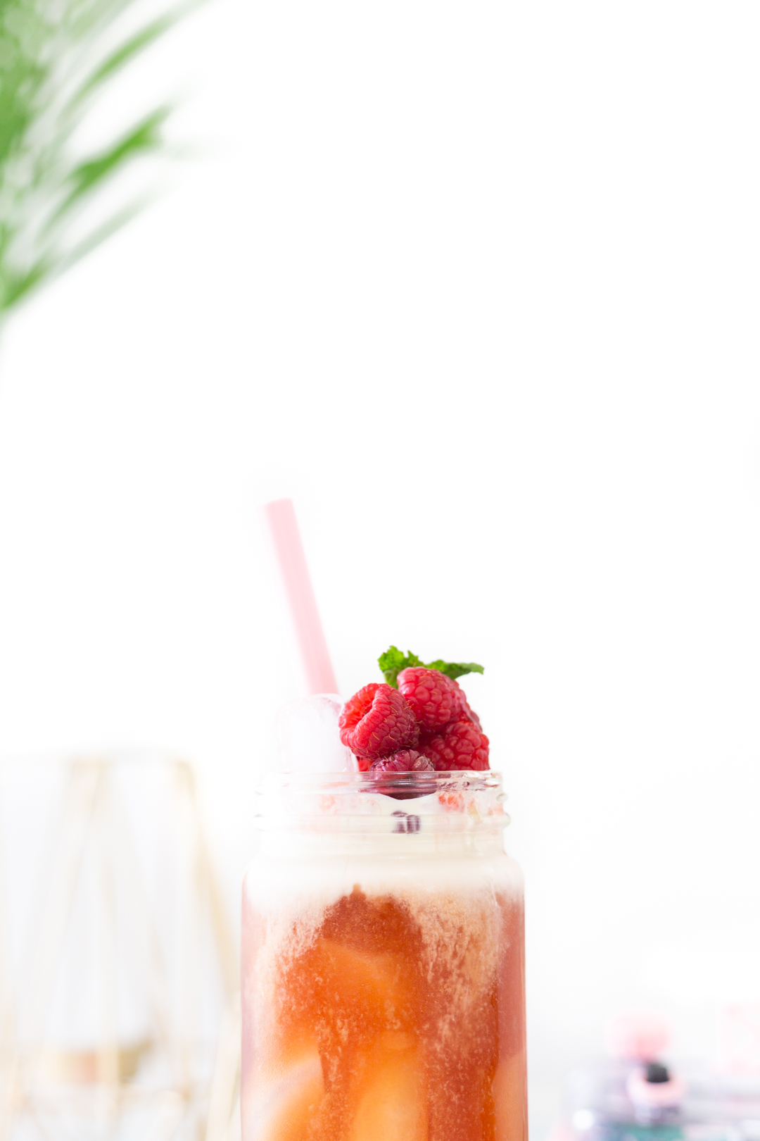 glass of iced tea with fresh raspberries and mint on top