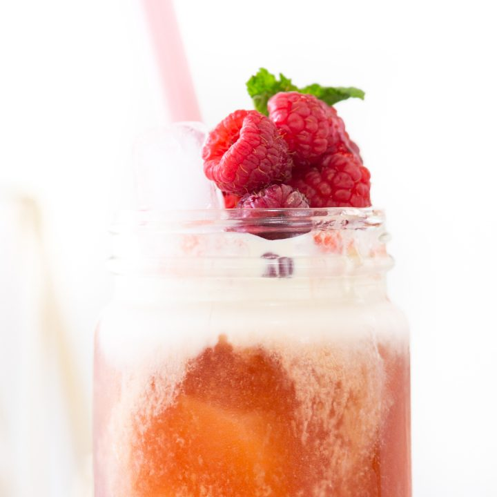 creamy raspberry tea topped with fresh fruit and herbs.
