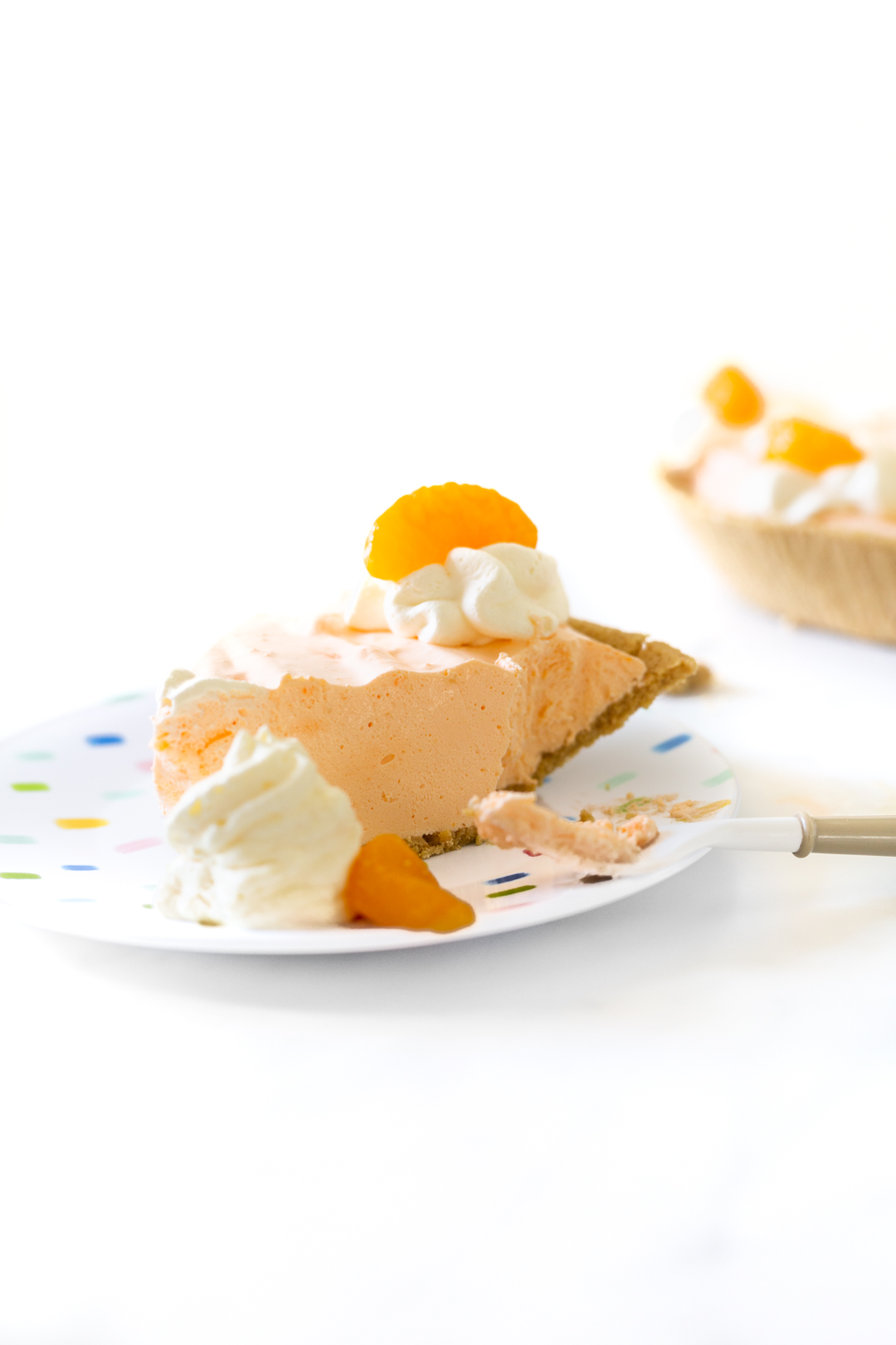 rich summer pie, slice shown on a plate with whipped cream and mandarin orange