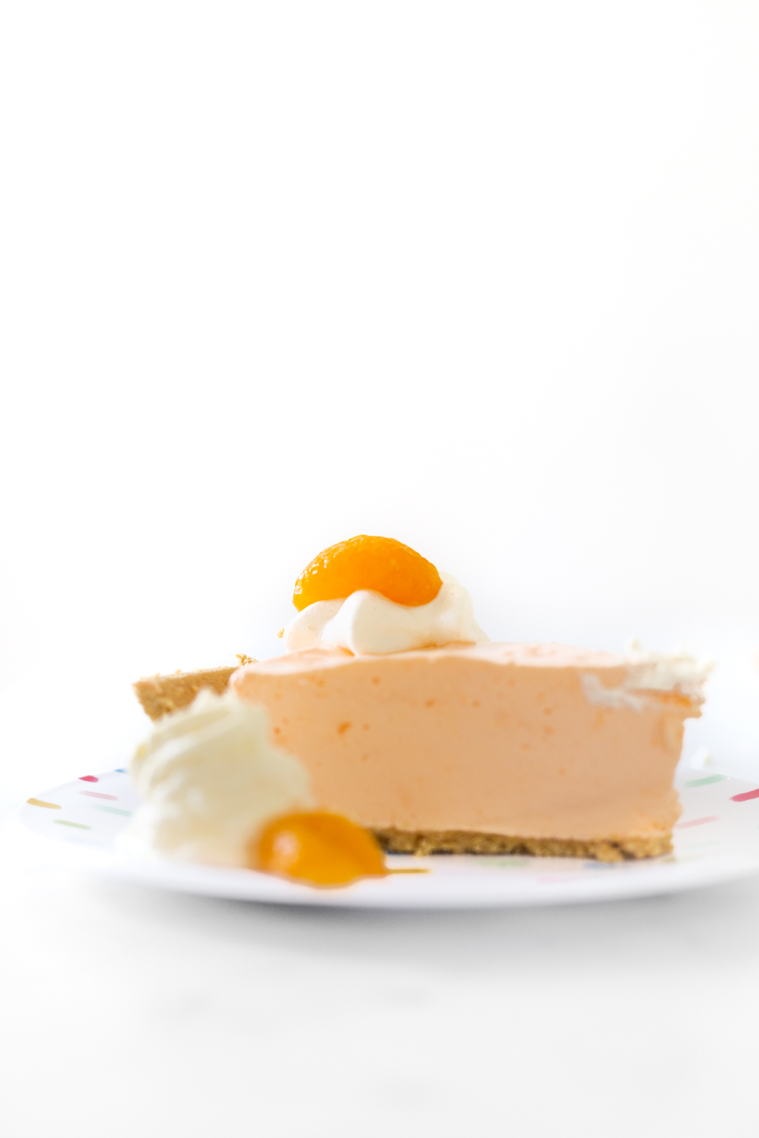 slice of pretty orange pie and topped with fruit garnish