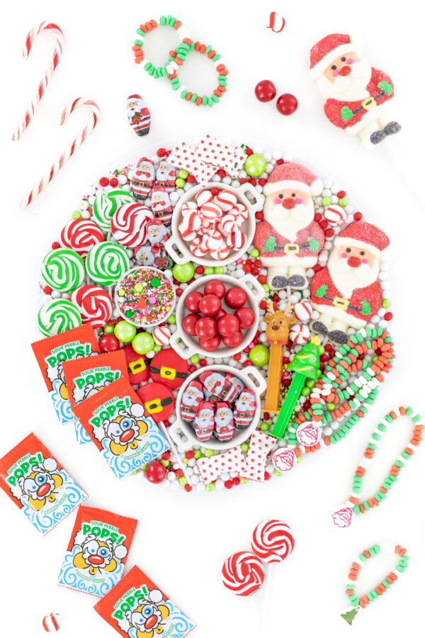 fun christmas candy board with red and green candies. flat lay style photo with candies displayed all over the table.