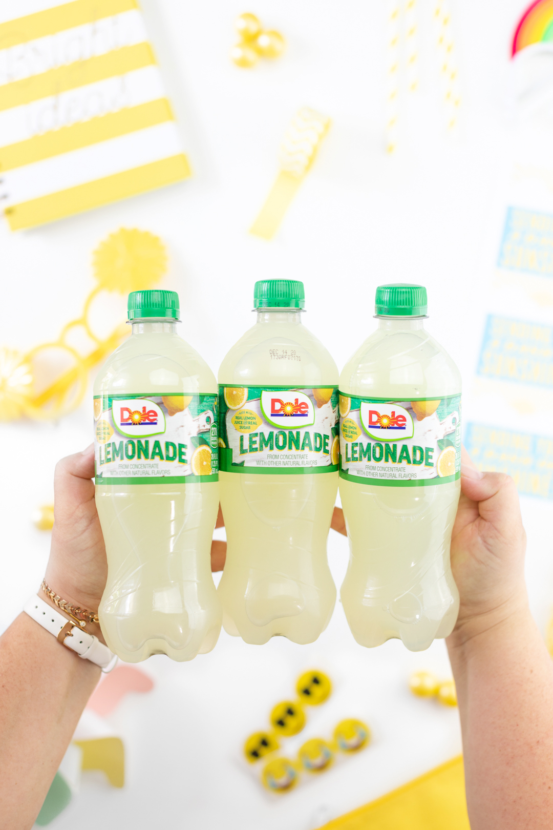 woman holding three single serve bottles of dole lemonade
