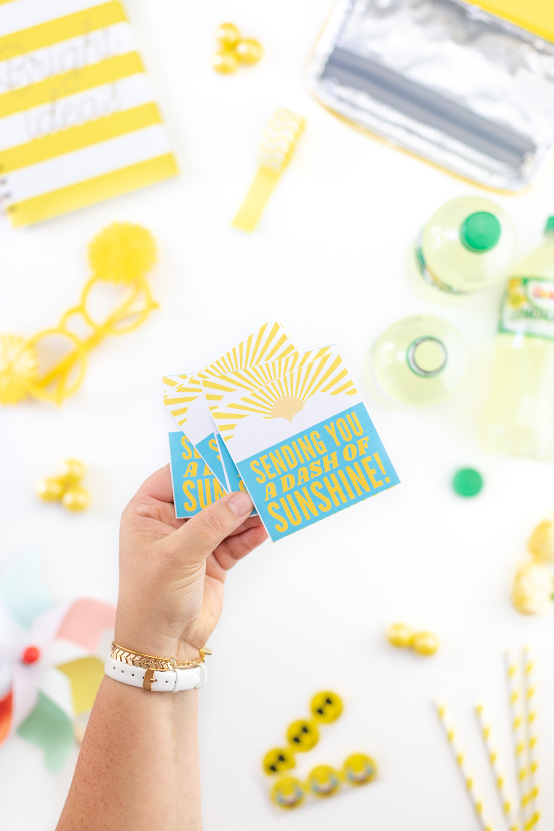 holding printed gift tags that read sending you a dash of sunshine