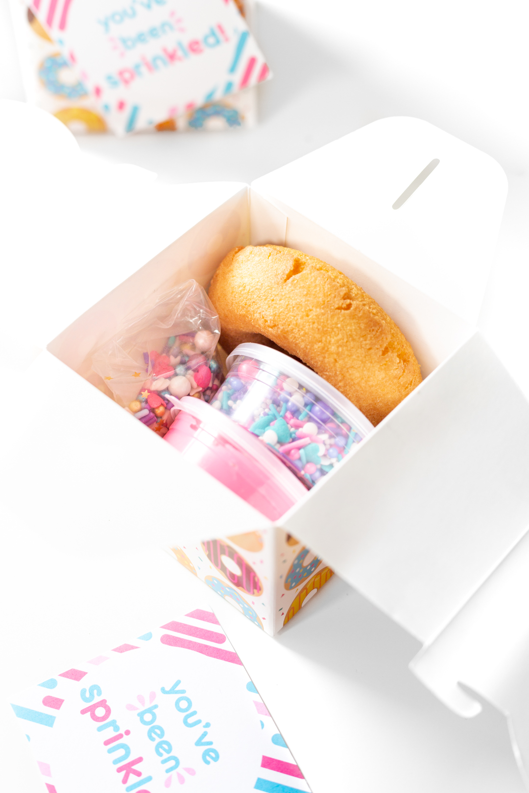 tiny donut decorating kit with containers of sprinkles and icing and a plain donut.